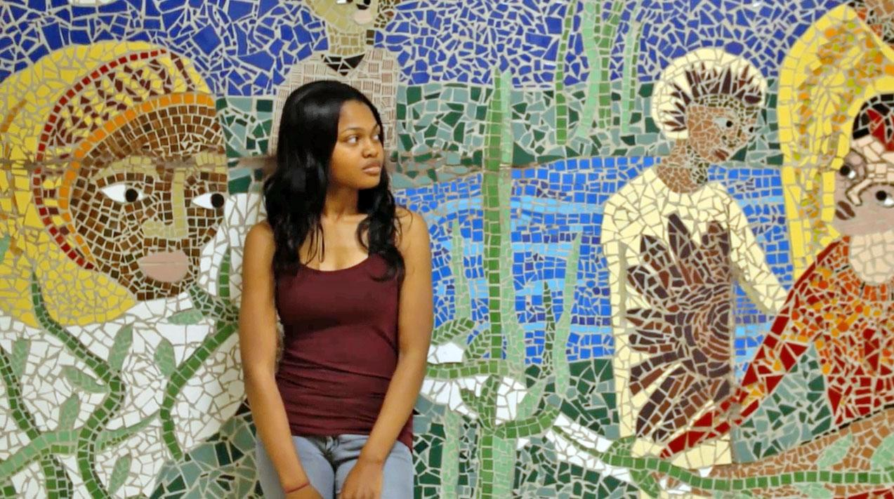 Photo of Destinee Bronson in front of mosaic.