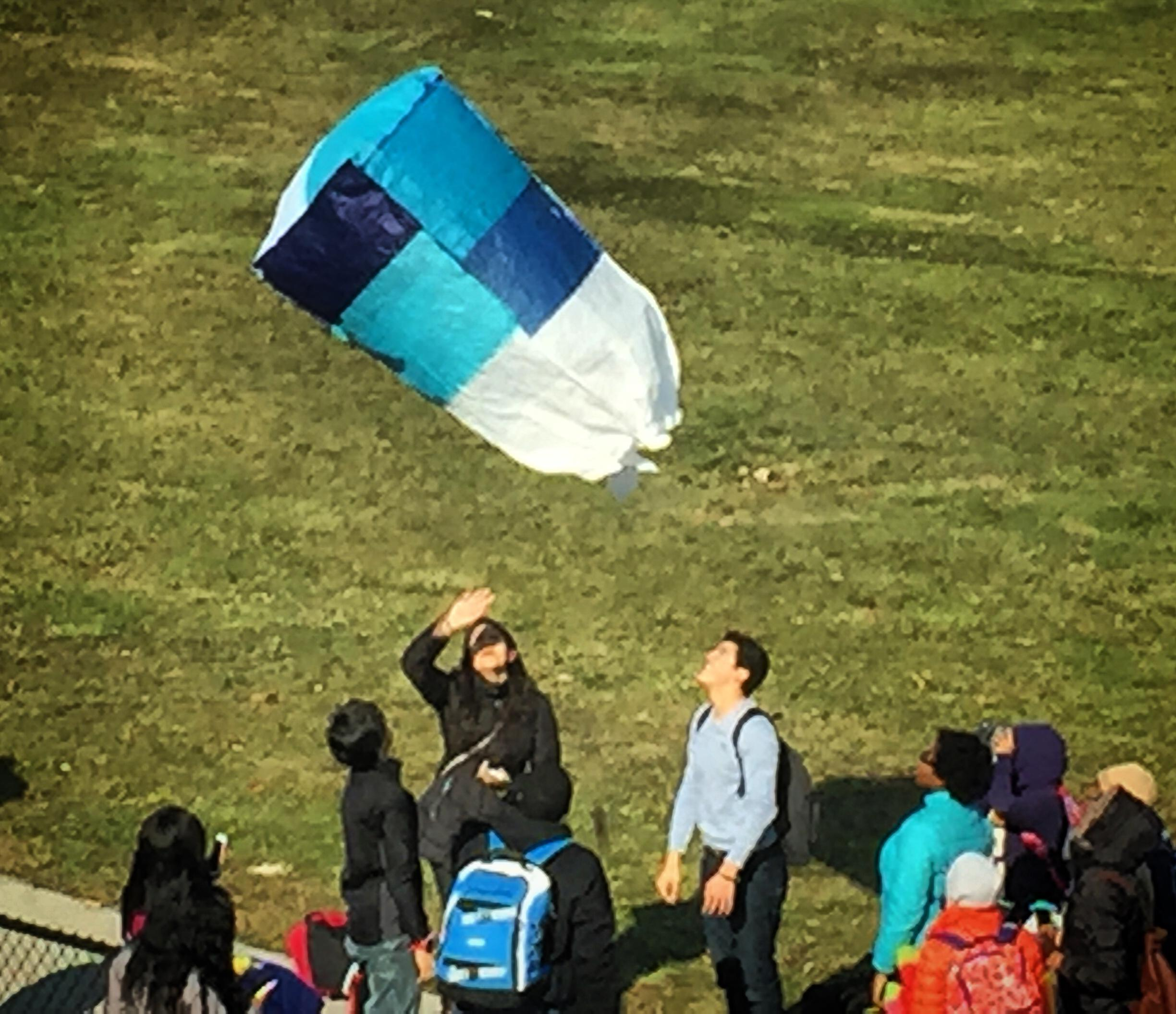 Ms. Zayed's students flying hot air balloons made of tissue paper out in the football field.