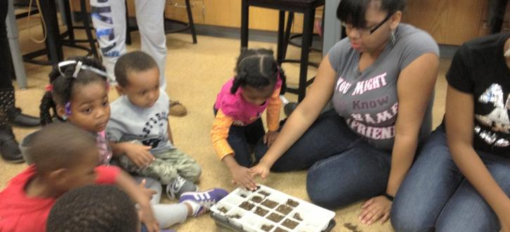 Photo of nursery children planting seeds with Brooks students.