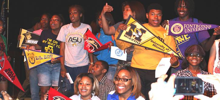 Photo of students holding banners from their future colleges.