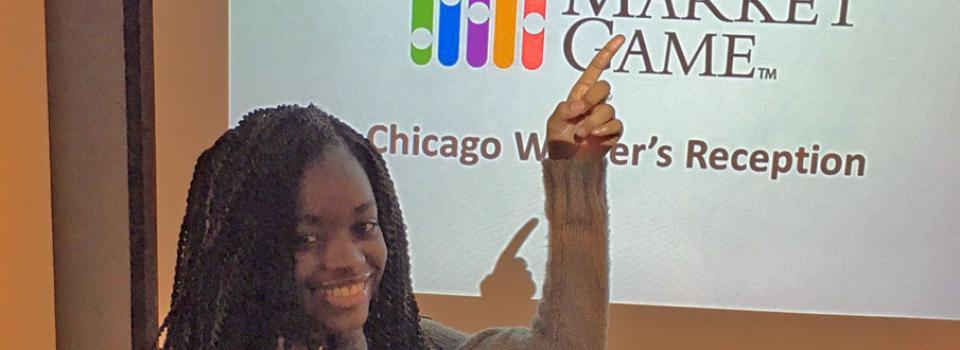 Photo of Dartonya Wright pointing to screen with logo.
